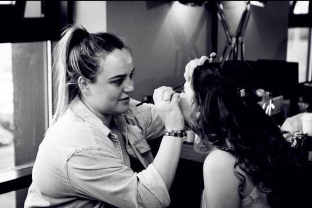 Black and white image of a young person having their make up done